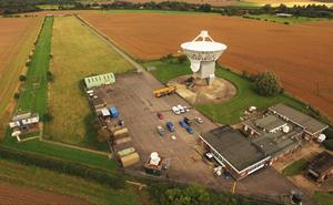 Aerial view of Chilbolton Observatory with buildings and a large white antenna.