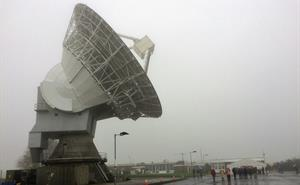 Visitors walk through the rain in front of the 25m dish