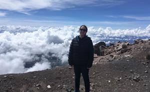Eimear Gallagher is standing on the summit of Volcan Sierra Negra, at an altitude of 4600m! Eimear is above the clouds .
